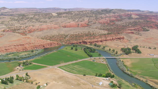 vidéos et rushes de ws aerial view over big horn river and desert mountains with landscape / wyoming, united states - wyoming
