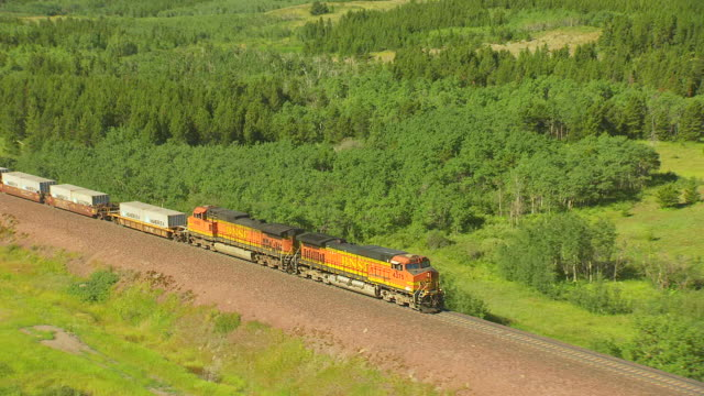 MS AERIAL TS ZO View over BNSF locomotive and lake in Glacier National Park / Montana, United States