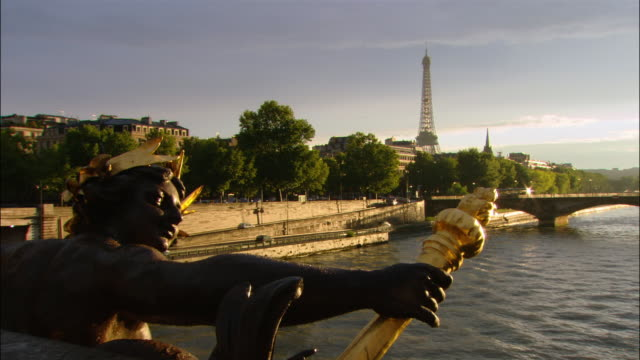 view over bronze statue on pont alexandre iii over seine of eiffel tower in distance / zoom in to tower / paris, france - pont alexandre iii stock videos & royalty-free footage