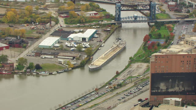 ms zo aerial view over buildings and bulk carrier in cuyahoga river near oil tank farm / cleveland, ohio, united states - fiume cuyahoga video stock e b–roll