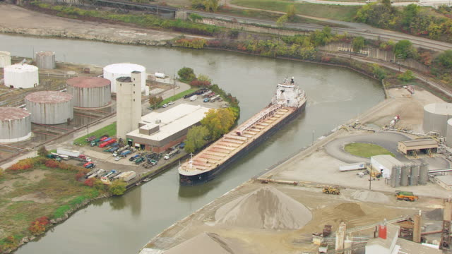 ms ds zo aerial view over bulk carrier calumet in cuyahoga river near oil tank farm and surrounding area / cleveland, ohio, united states - fiume cuyahoga video stock e b–roll