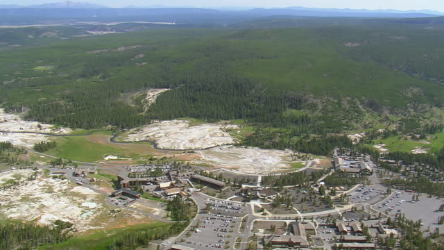 ws aerial view over cars parked near old faithful and dense forest / wyoming, united states - old faithful stock videos & royalty-free footage