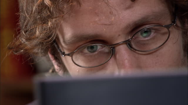 View over computer monitor of man reading screen / removing glasses and rubbing eyes in exhaustion / looking back at screen