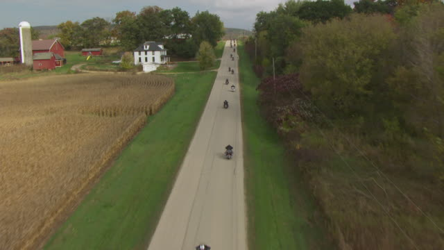 WS AERIAL TS View over country road in Sauk County and tilt up to motorcycle riders driving country road along farms