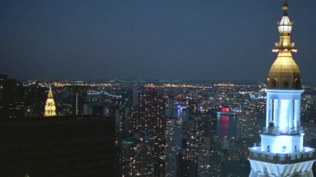 stockvideo's en b-roll-footage met aerial view over cupola of metropolitan life tower at night with empire state building in background / new york, new york, usa - 1990 1999