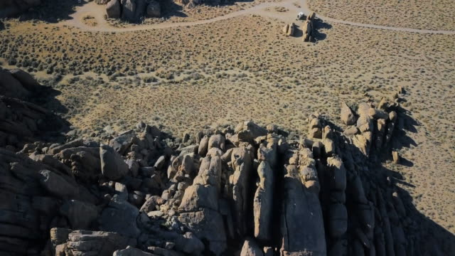 view over desert and rocky outcroppings - hügelkette stock-videos und b-roll-filmmaterial