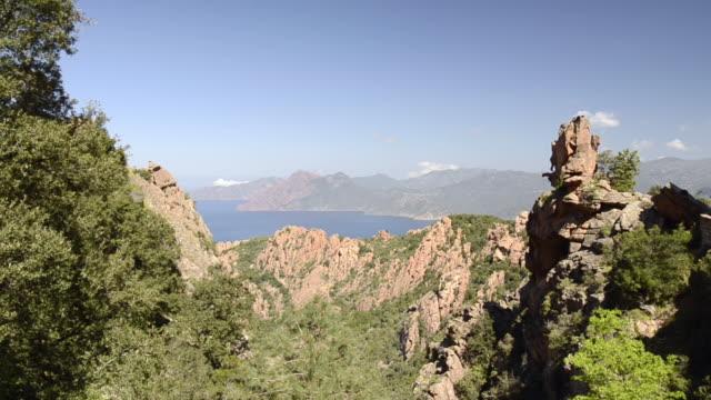 vidéos et rushes de ws pan view over fantastic rock landscape of calanche of piana to sea, unesco world heritage site / porto, corsica, france - french culture