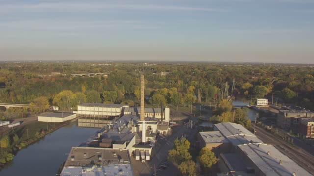 WS AERIAL TD View over Fox River and CU fly over smokestack at Fox River Paper Mill / Appleton, Wisconsin, United States