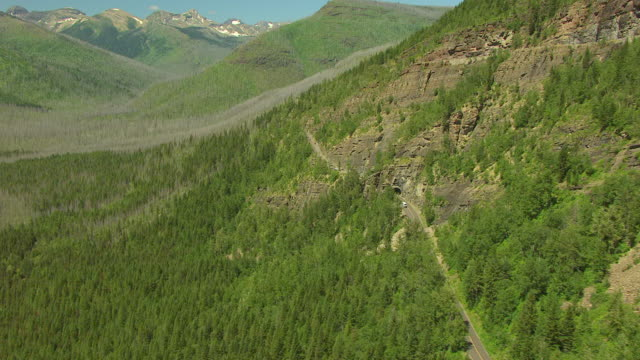 ws aerial view over glaciers towering over road in glacier national park / montana, united states - アメリカグレイシャー国立公園点の映像素材/bロール
