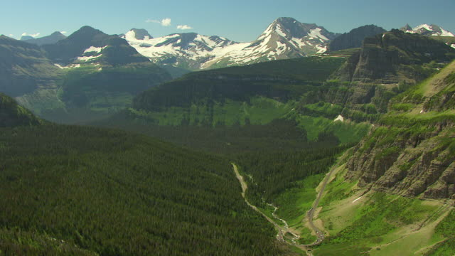 WS AERIAL View over green canyon with snowy glaciers in Glacier National Park / Montana, United States