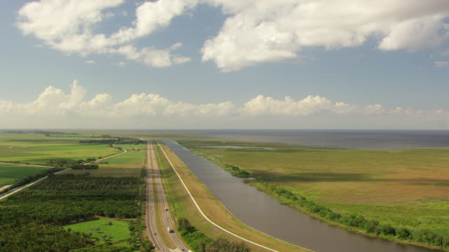 WS AERIAL View over Herbert Hoover Dike to lake / Lake Okeechobee, Florida, United States