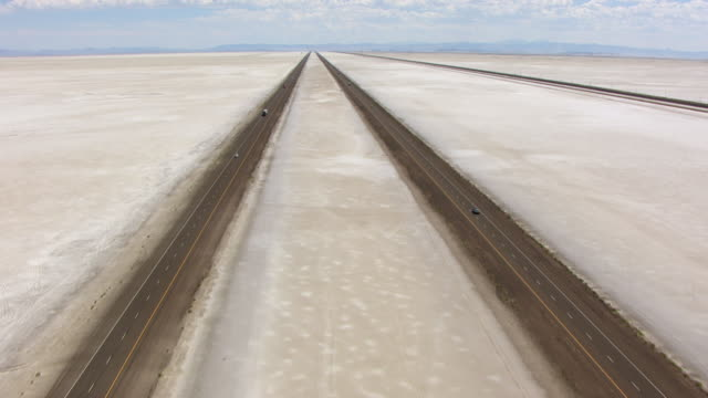 ws aerial view over highway 80 at bonneville salt flats and follow with mountains / utah, united states - salt flat stock videos & royalty-free footage