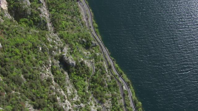 ws aerial view over highway parallel to lake / lake garda, trentino, verona, brescia - トレンティーノ点の映像素材/bロール