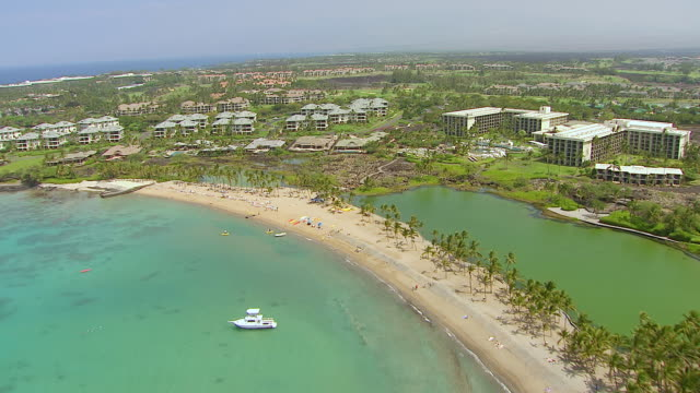 ws aerial view over hotels intermixed with land lava flow on big island / hawaii, united states - ハワイ島点の映像素材/bロール