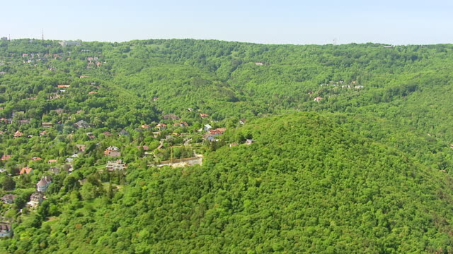 WS AERIAL View over houses in city with dense forest / Budapest, Hungary