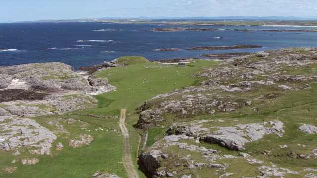 WS AERIAL View over island on west coast showing croft farm house and sheep then out over sea rising above Sound of Gunna / Isle or island of Tiree, Argyll and Bute, Scotland