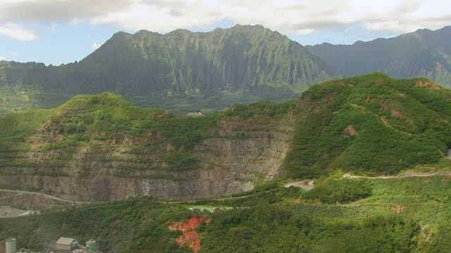 ws zi aerial view over large mountains covering in green grass and bushes on island of oahu with mining plant / hawaii, united states - oahu stock videos and b-roll footage