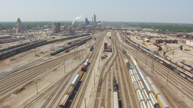 WS AERIAL POV View over large train yard and railway tracks to smoke coming out of smoke stack / Decatur, Illinois, United States