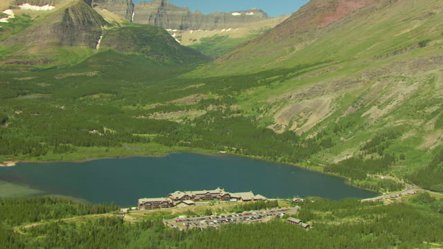 ws aerial zi view over many glacier hotel and swift current lake with glaciers at glacier national park / montana, united states - glacier national park us stock videos and b-roll footage