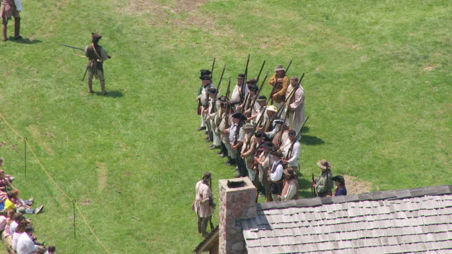 ms ts aerial view over militia standing in line and shawnee men crouching behind wood log and fires gun at fort randolph reenactment / point pleasant, west virginia, united states - american revolution stock videos & royalty-free footage