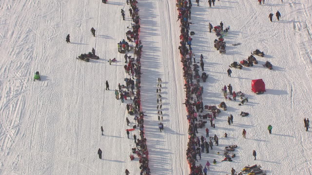 WS AERIAL TS View over musher and dogsled team racing through trail with fans to side during Iditarod Trail Sled Dog Race / Willow, Alaska, United States