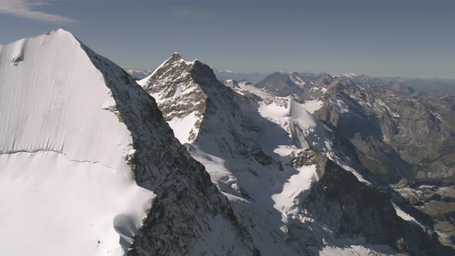ws aerial view over northeastern ridge of monch with white northeast face and summit of monch, aletsch region and summit of jungfrau / monch, bern, switzerland - berg jungfrau stock-videos und b-roll-filmmaterial