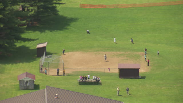 WS AERIAL View over people playing baseball on field at Green Bank Elementary and Middle School in Pocahontas County / Green Bank, West Virginia, United States
