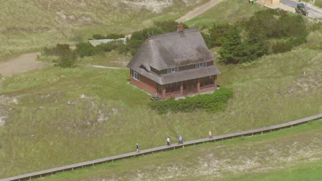 ws aerial view over people walking on wooden track / amrum, schleswig holstein - schleswig holstein stock videos & royalty-free footage