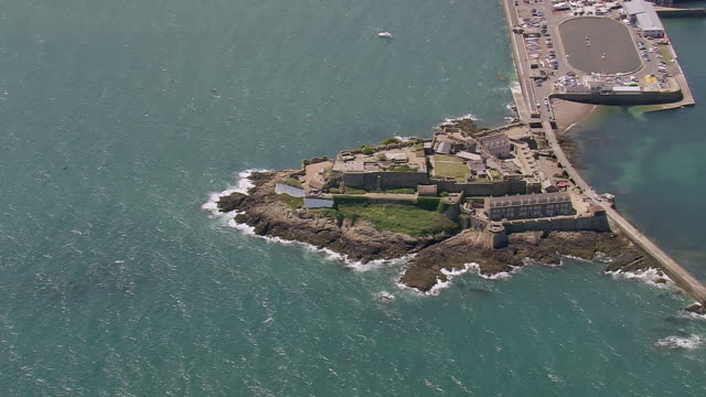 ws aerial view over pier and coastline / guernsey, channel isles - guernsey stock-videos und b-roll-filmmaterial