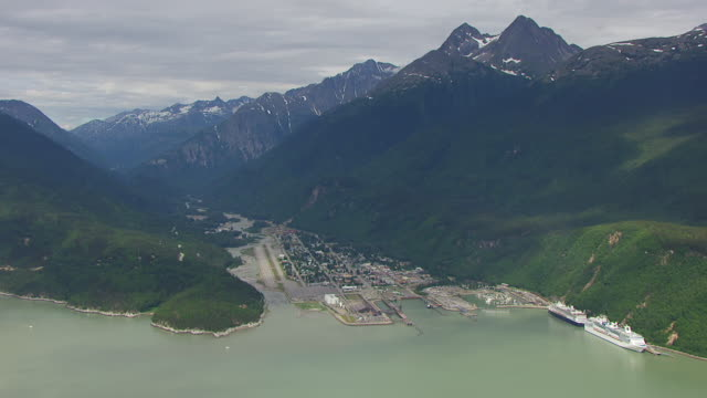 vídeos de stock, filmes e b-roll de ws aerial view over port and face mountain / skagway, alaska, united states - skagway