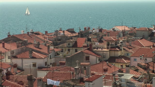 stockvideo's en b-roll-footage met ha ws view over rooftops of sailboat floating across adriatic sea / piran, slovenia - onbekend geslacht