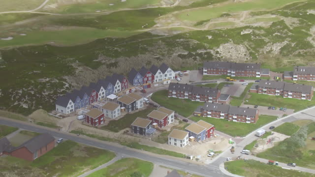 ws aerial zi view over row houses besides cars running on street with cloud shadow over / sylt, schleswig holstein - insel sylt stock-videos und b-roll-filmmaterial