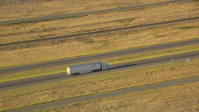MS AERIAL TS ZO View over semi truck driving on highway with fields / Montana, United States