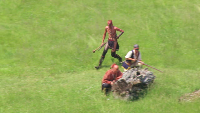 MS TS AERIAL View over Shawnee runs to join other soldiers behind tree stump and shoots guns at Fort Randolph Reenactment / Point Pleasant, West Virginia, United States