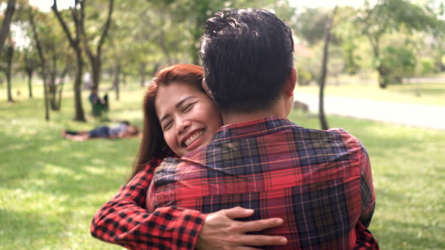 view over shoulder : couple smiling and hugging in park - coppia di età matura video stock e b–roll
