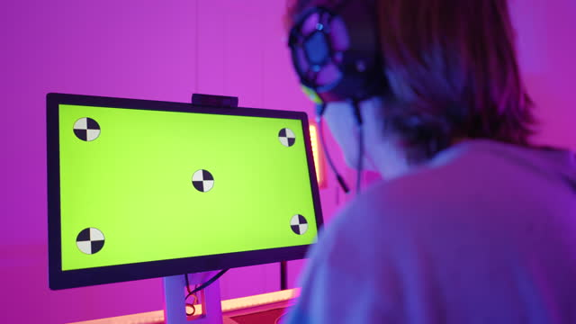 view over shoulder of caucasian young man, a gamer, streamer concentrate to play a multiplayer online game, live streaming on computer pc, screen show green screen,  positive emotion in the multicolor decorated room as cyberpunk - game show stock videos & royalty-free footage