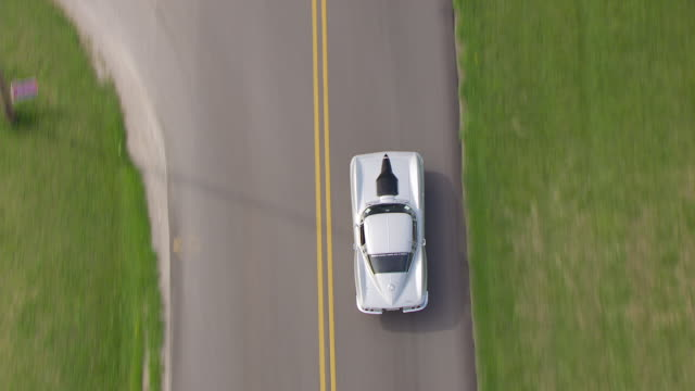 vídeos de stock, filmes e b-roll de cu aerial ts view over silver corvette driving on road / bowling green, kentucky, united states - carro esportivo