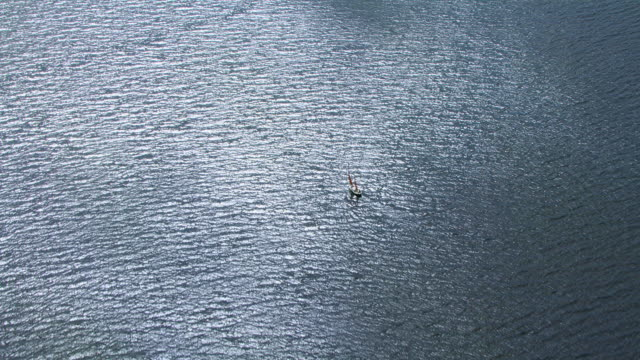 WS AERIAL View over single sailboat or yacht in silvery sea on west coast / Isle or island of Mull, Argyll and Bute, Scotland