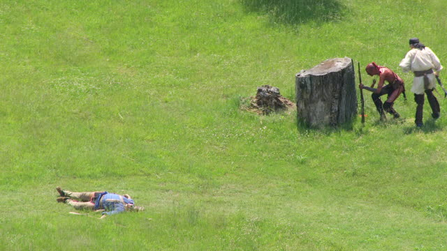 stockvideo's en b-roll-footage met ms ts zo aerial view over soldier on ground with fallen warrior and running behind tree stump and field at fort randolph reenactment / point pleasant, west virginia, united states - boomstronk