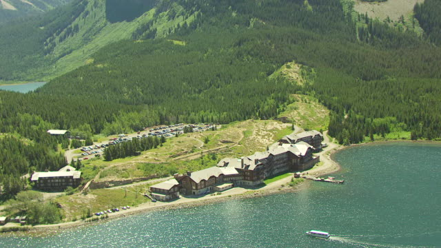 ws aerial view over swift current lake and many glacier hotel in glacier national park / montana, united states - glacier national park us stock videos and b-roll footage