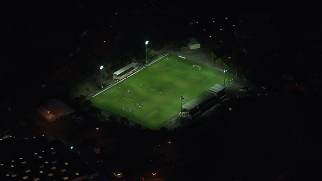 vídeos y material grabado en eventos de stock de ws aerial view over teams playing football on ground in saint raphael at night / provence alpes cote d'azur, france - var