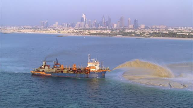 vidéos et rushes de ws pov aerial view over the island construction project / dubai, united arab emirates - île