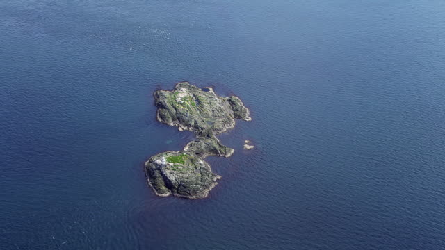 WS AERIAL View over tiny island with lighthouse on west coast / Isle or island of Jura, Argyll and Bute, Scotland