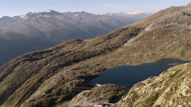 ws aerial view over totesee reservoir on grimsel pass with restaurants and pass road with rhone valley / grimsel pass, valais, switzerland - kanton wallis stock-videos und b-roll-filmmaterial