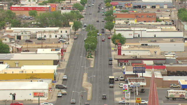 WS AERIAL View over town main street with stores and cars driving / Roswell, New Mexico, United States