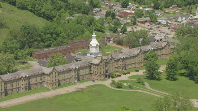 ws aerial view over trans allegheny lunatic asylum in lewis county and clock tower / weston, west virginia, united states - ospedale psichiatrico video stock e b–roll