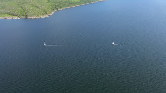 vídeos de stock e filmes b-roll de ws aerial ds view over two distant sailboats or yachts on west coast / isle or island of mull, argyll and bute, scotland - ilha mull