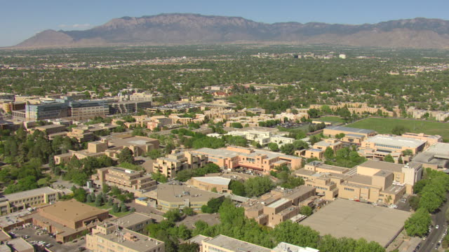 ws aerial view over university of new mexico campus with pueblo style campus buildings and mountains / albuquerque, new mexico, united states - albuquerque new mexico stock videos & royalty-free footage