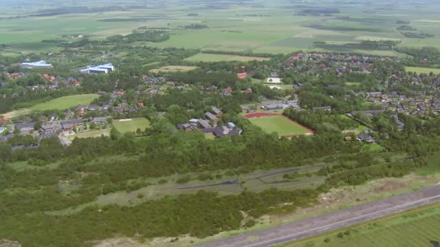 ws aerial view over village at north sea / sankt pete ording, schleswig holstein - schleswig holstein stock-videos und b-roll-filmmaterial