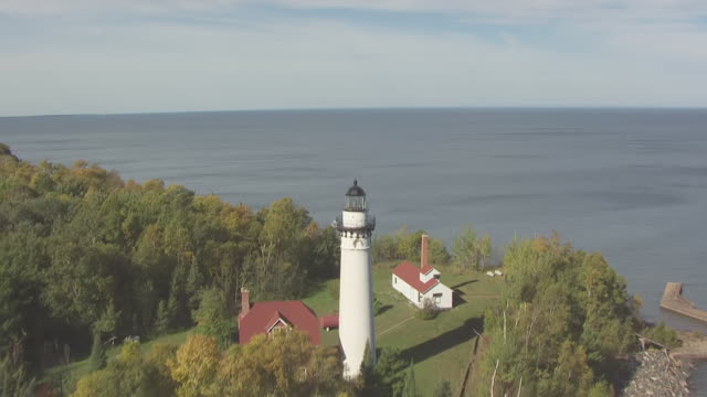 ws aerial tu view over water to pull up over lighthouse on outer island in apostle islands / wisconsin, united states  - lago superiore video stock e b–roll